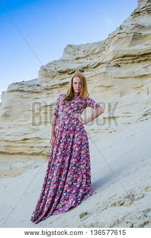 Beautiful slim young girl wearing long colorful dress in the desert. Fashion and glamour concept. Toned.