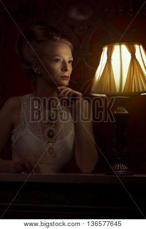 Woman In Victorian Style And Vintage Room With Lamp Beside Her