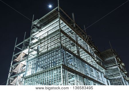 night view of metal framework of tall building under construction with lights illuminating detail