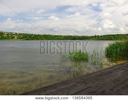 Lake with transparent water and pier for fishermen