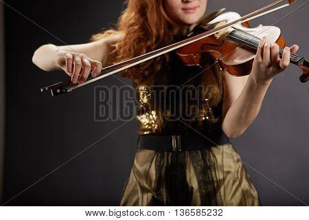 Beautiful young woman playing violin. Music symphony.