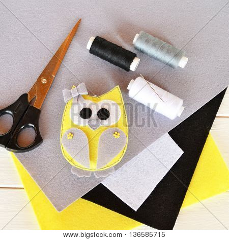 Cute felt owl toy decorated with bow and buttons. Stuffed animal owl on wooden background. Home decor plush toy. Felt sheets, scissors, thread, needle, pins. Top view. Adorable sewing project for kids