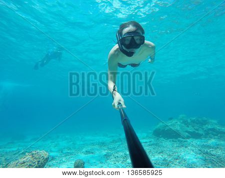 Underwater selfie shot with selfie stick. Deep blue sea. Wide angle shot.
