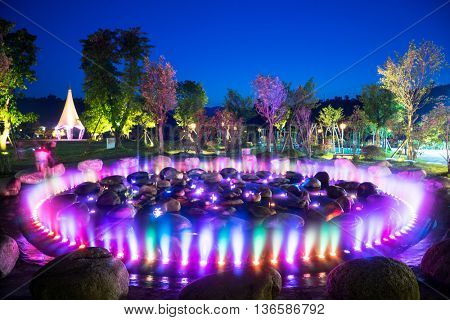 beautiful round fountain with colorful light and stones in park
