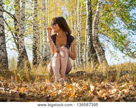 smiling woman on a background of autumn forest