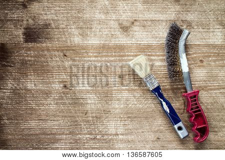 Paintbrush and wire brush on the old wooden background with copy-space