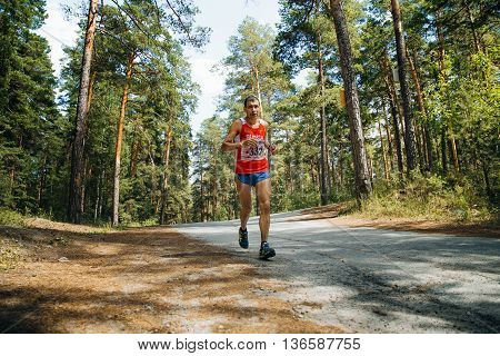 Miass Russia - June 26 2016: male athlete running down road in woods during Marathon