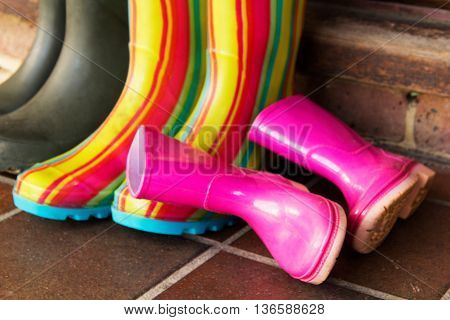 Colourful wellington boots left outside on a doorstep