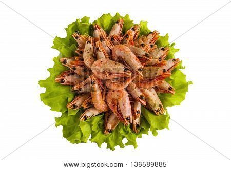 Big boiled shrimps on green lettuce. Isolated on white background top view.