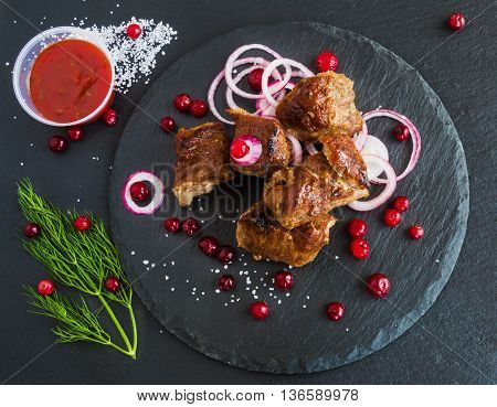 Grilled pork meet (shashlik) on black stone background. Fresh onion cranberries and dill. Top view.