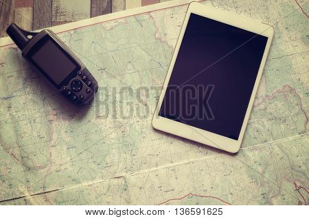 Travel planning. GPS navigator and tablet are on the paper map. Flat lay. Toned image