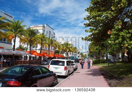 MIAMI BEACH, UNITED STATES - FEBRUARY 11: People and cars move down the Ocean Drive touristic attraction street on 11th of February, 2016 in Miami Beach.
