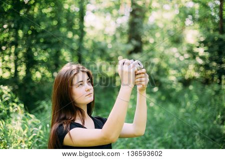 Red-haired Caucasian Girl Young Woman Photographer Taking Pictures The Old Retro Vintage Film Camera In Summer Green Forest. Girl Dressed In A Black T-shirt