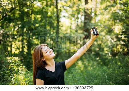 Happy Red-haired Caucasian Girl Young Woman Photographer Taking Selfie And Pictures The Old Retro Vintage Film Camera In Summer Green Forest. Girl Dressed In A Black T-shirt