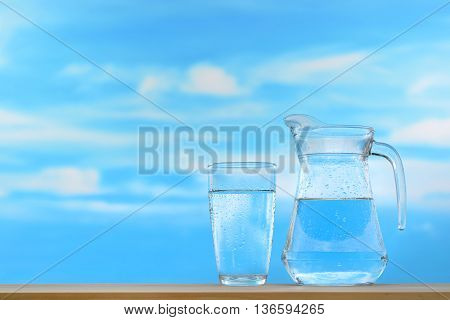 Fresh and clean drinking water in jug and glass on sky background