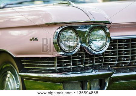 MINSK BELARUS - MAY 07 2016: Close-up photo of pink Cadillac de Ville. Detail on the headlight of vintage classic car. Selective focus.