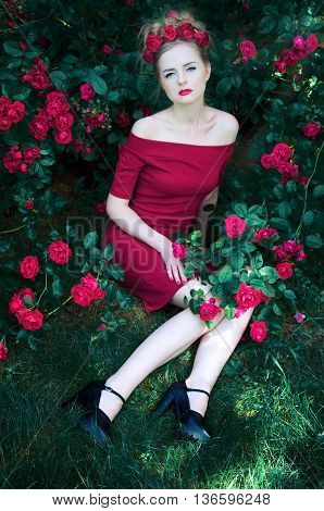 Summer portrait of beautiful blond woman with magenta roses