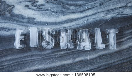 Eiskalt caption made of ice cubes on dark marble meaning ice cold in German