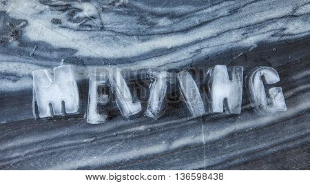 Melting caption made of ice cubes on dark marble