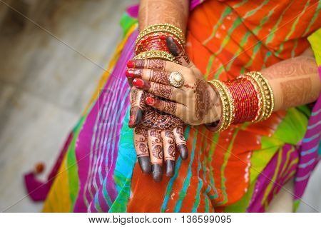 Top view of a Indian Hindu woman'd hand with henna tattoo and red bangles