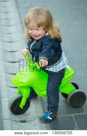 Little boy with blond long hair cries and sits on bicycle outdoor on grey street pavement