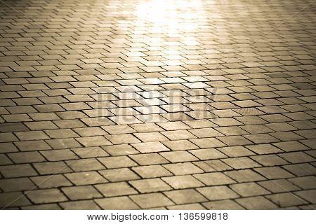 Beige brick rectangular paving stones on cobblestone pavement background