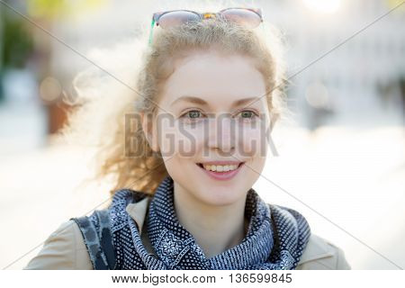 Young woman with pretty face and curly long hair with sunglasses on head smiles outdoor
