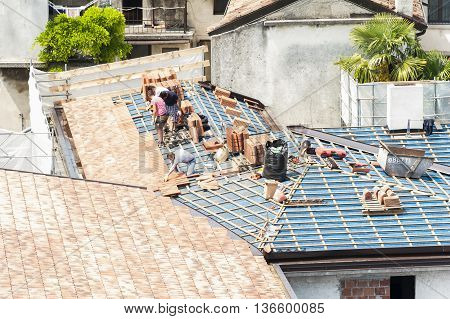 Udine , Italy - May 26 , 2016 : Construction site. Masons to work on the roof for laying tiles