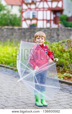 Little blond kid boy walking with big umbrella outdoors on rainy day. Child having fun and wearing colorful waterproof clothes and rain boots.
