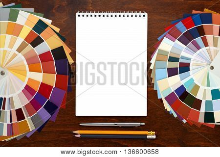 Designer working place. Color palette guide on the wooden background and notepad. mockup template. Top view