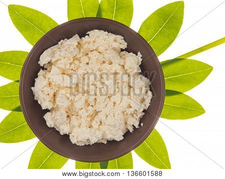 fresh homemade white cheese in brown clay bowl on a background of green leaves in the shape of a flower isolated on white background