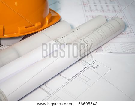 Architect rolls and plans technical project drawing (Selective focus)