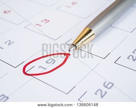 Close up pen put on calendar desk with red ink circle on 19 date (Selective focus)