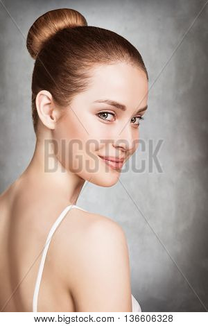 Beautiful face of young woman with clean fresh skin over gray wall background