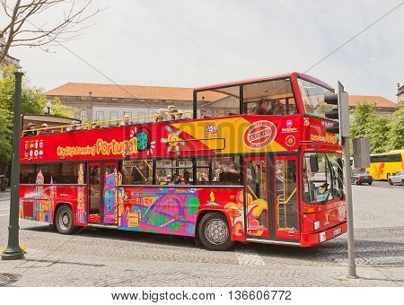 PORTO PORTUGAL - MAY 26 2016: World famous double-decked open top red Sightseeing Bus on Liberdade Square in the historical center of Porto Portugal (UNESCO site)