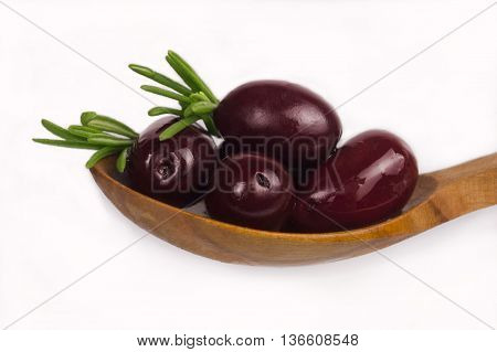 Red olives over spoon. Olive and rosemary isolated on white background.