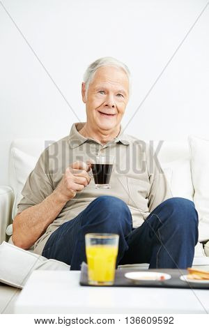 Old man drinking coffee for breakfast in a nursing home