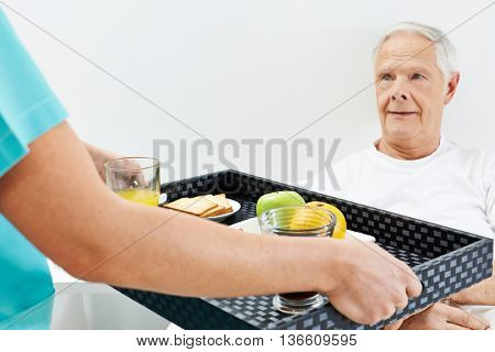 Senior man getting breakfast in bed in a nursing home