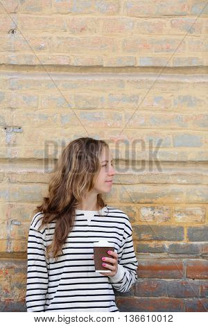 Coffee On The Go. Young Woman On The Background Old Wall