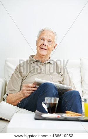 Senior man with a newspaper thoughtfully looking up