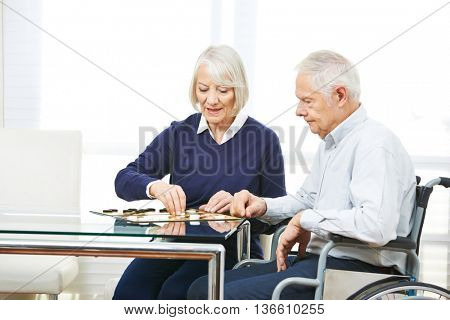 Happy senior couple playing checkers in nursing home