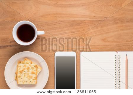 Mobile phone paper notebook pencil plate of crackers and cup of coffee or tea are arranged in simple flatlay design on wood table with copyspace on top