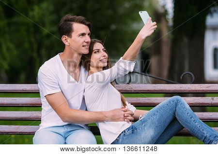 beautiful young couple sitting on a bench in the park