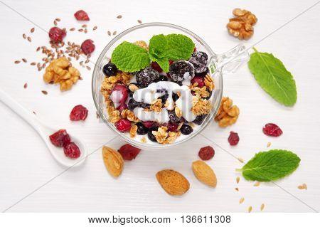 Healthy breakfast granola with yogurt nuts seeds and berries. Top view.