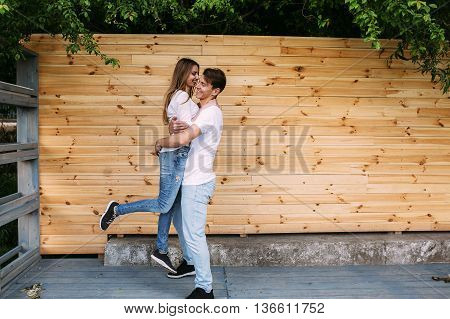beautiful young couple posing on a background of a wooden wall at the camera