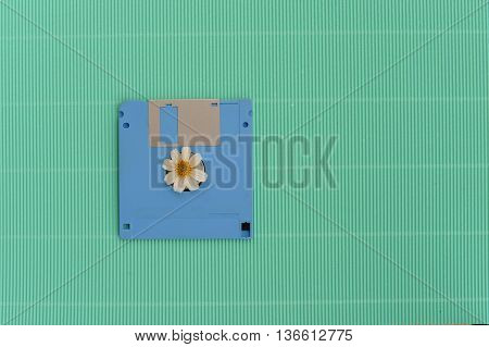 blue floppy disk and white flower on green vintage background