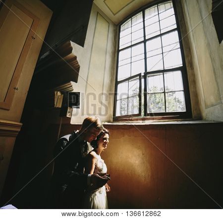 Bride and groom posing on the background of a large window