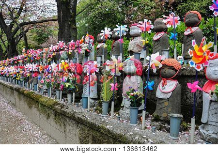 Stone dolls wearing diffent cloths in temple Japan