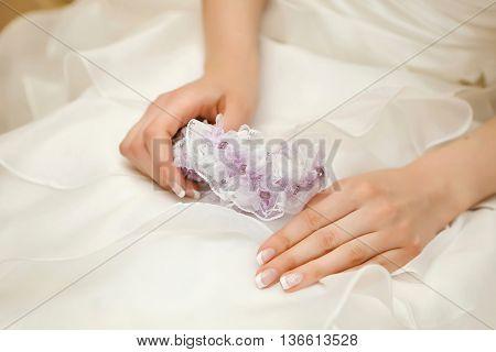 wedding garter in the hands of the bride