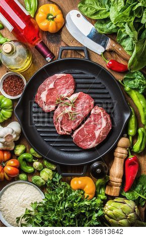 Ingredients for cooking healthy meat dinner. Raw uncooked beef steaks with vegetables, rice, herbs, spices and wine bottle over rustic wooden background, cast irom grilling pan in center. Top view